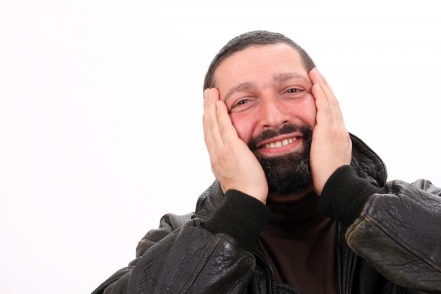 頬の髭を手で覆う男性