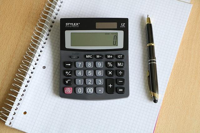 ノートの上に電卓とペン