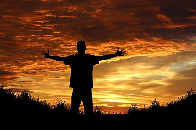 日の出に向かって手を広げている男性