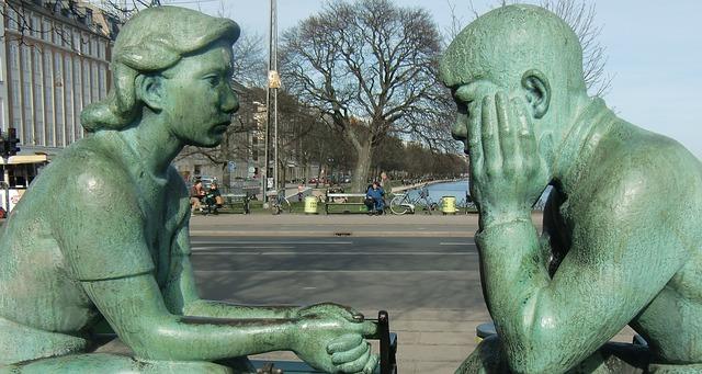 女性と男性が座って話をしている像