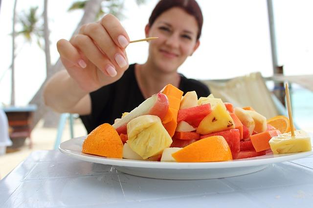 果物がのった皿に爪楊枝を近づける女性