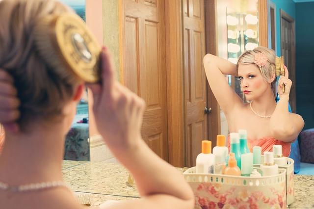 鏡に向かって自分のヘアメイクを施す女性