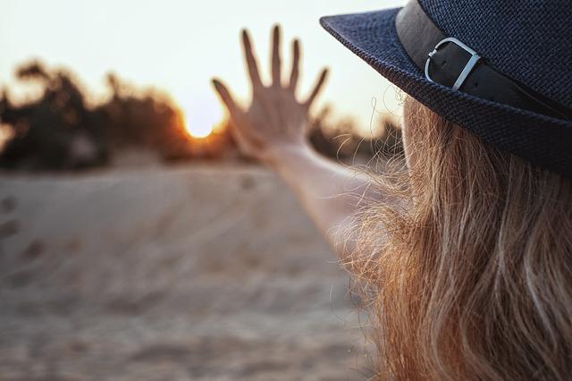太陽に向かってストップジェスチャーしている女性
