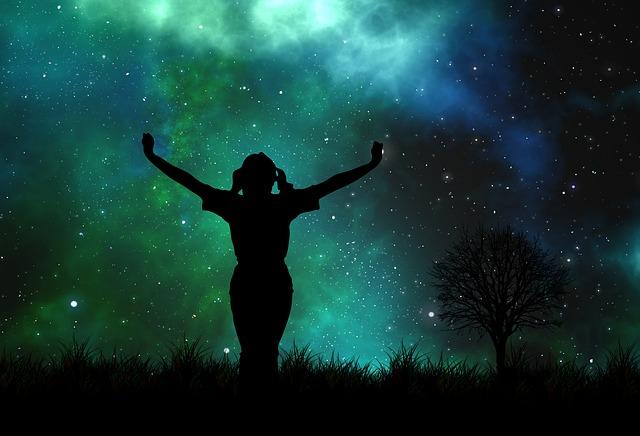 星に向かって手を広げている女性