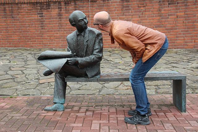 銅像の顔を覗き込む男性