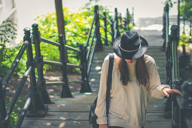 階段を上っている帽子をかぶった女性