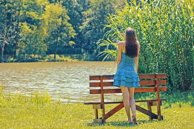 湖のほとりに立つ青いドレスを着た女性