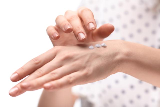 美白クリームを手に塗る女性
