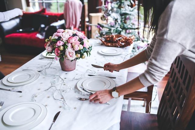 テーブルに食器を並べている女性