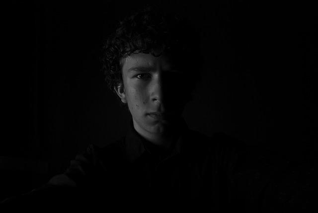 真っ暗なところで暗い顔をする男性