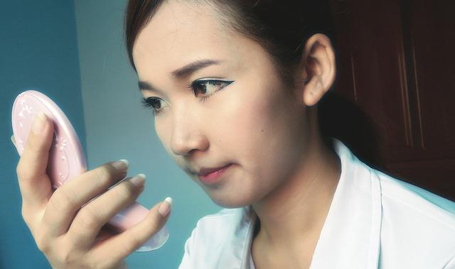 手鏡を持って自分の顔を見ている女性