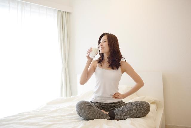 ベッドの上であぐらをかきお腹に手を当てて豆乳を飲んでいる女性