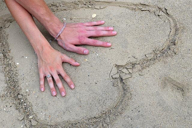浜辺のハートマークの中に男女の手