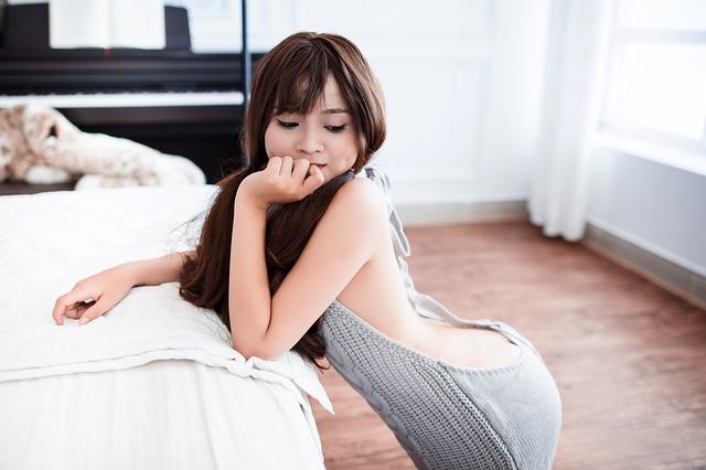 ベッドにいる背中のあいた鼠色の服を着ている女性
