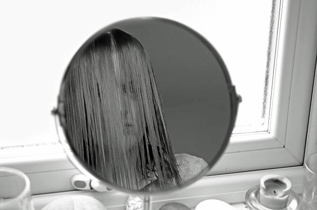 丸い鏡に映る自分を見つめる髪の毛が顔までかかっている女性