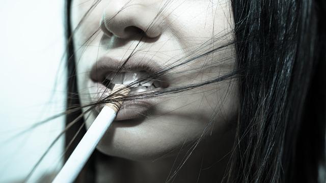 タバコを口にくわえる女性