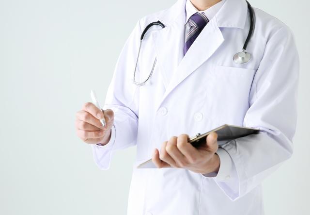 左手にカルテ右手にペンを持つ男性医師