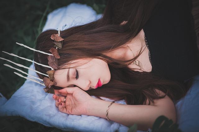 頭に葉の髪飾りを付けながら眠る美女
