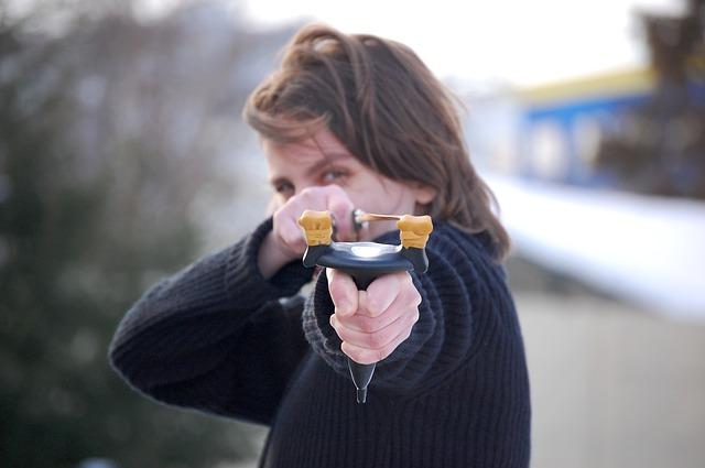 スリングショットを手に持つ女性