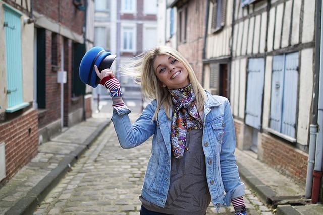 青い帽子をとる笑顔の女性