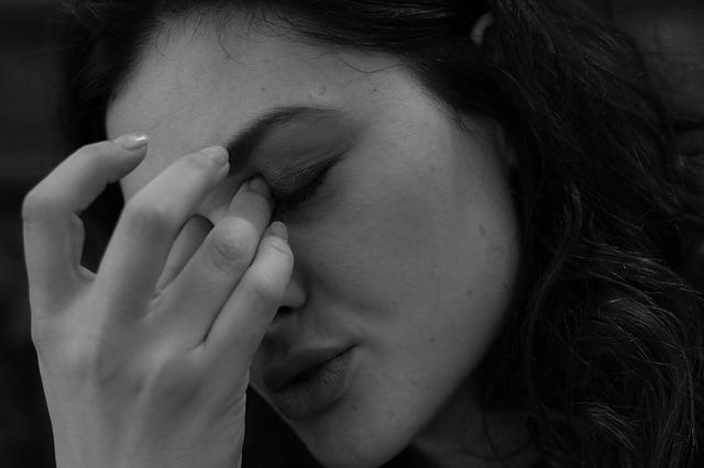 目に指をやり疲れている女性