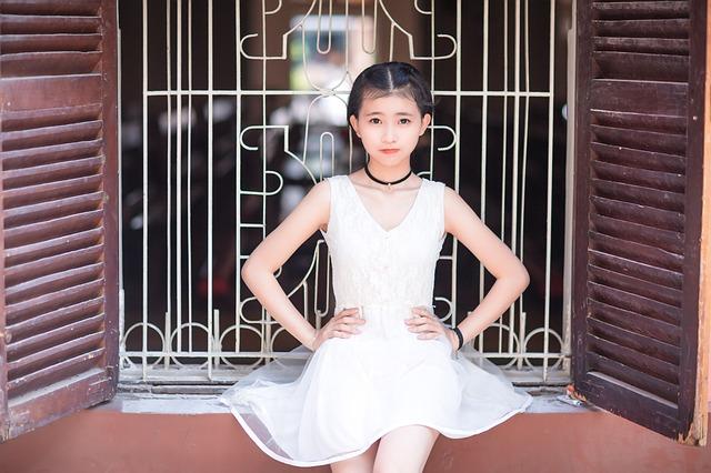 白いワンピースと黒いネックレスを付けている女の子