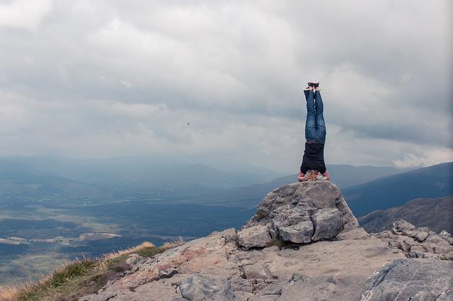 山の頂上で倒立する人
