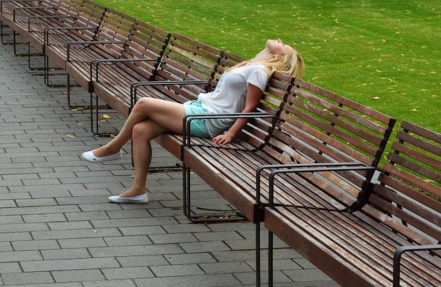 ベンチで空を見ながら休んでいる女性