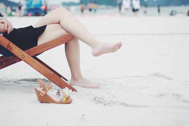 ビーチの砂浜の上で足をクロス
