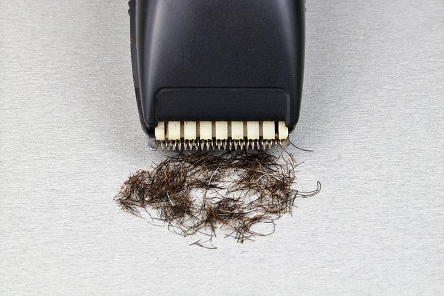 黒い電動シェーバーと沢山の黒い毛