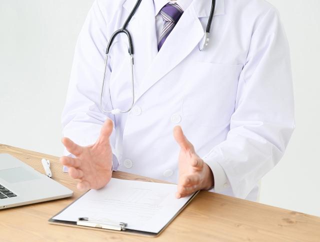 手を広げるジェスチャーをする男性医師