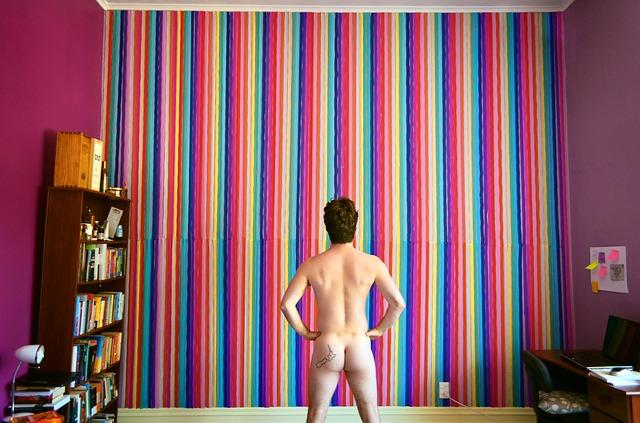 壁を見据える裸の男性