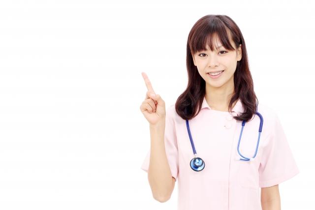 右手の人差し指を上に向ける女性看護師