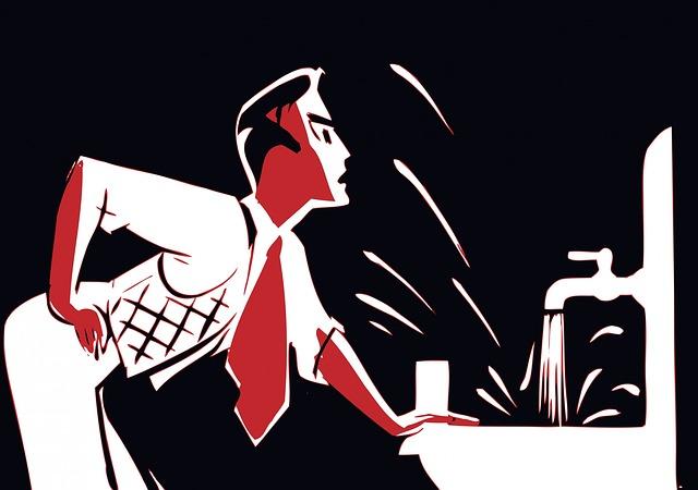 洗面所で鏡を見ている赤いネクタイをした男性