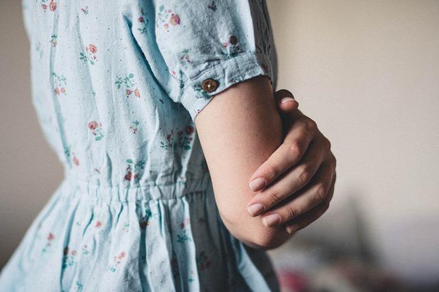 水色のワンピースを着た腕を前に組んでいる女性
