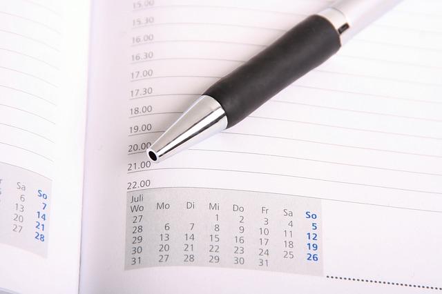 スケジュール手帳の上に取っ手のゴムが黒色の銀色ボールペン