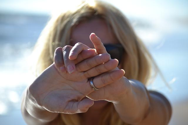 手の平をこちらに向けているサングラスをかけた女性