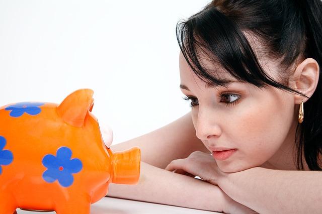 ピンク色の豚の貯金箱とそれを見る女性
