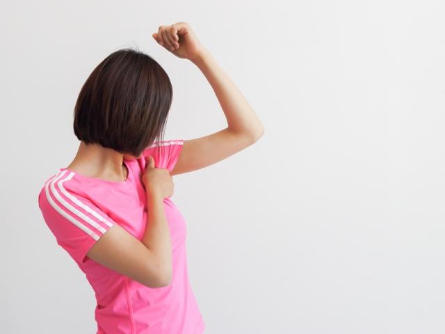 脇を見るピンク色の服を着た女性