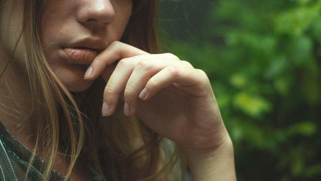 女性の口元と指