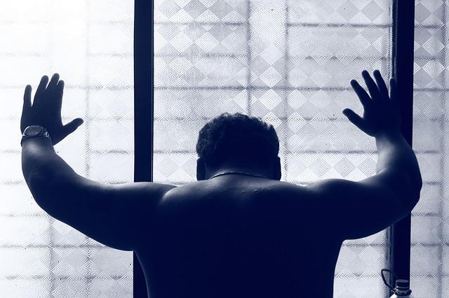 ガラスに手をついて悩んでいる男性