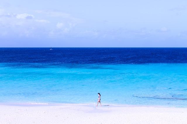 水着を着た女性が砂浜を歩く