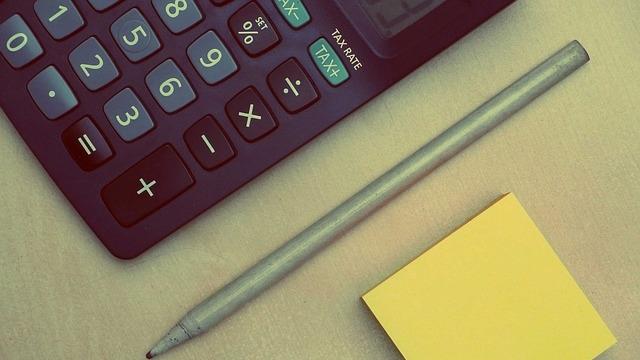 電卓とペンと黄色い付箋用紙