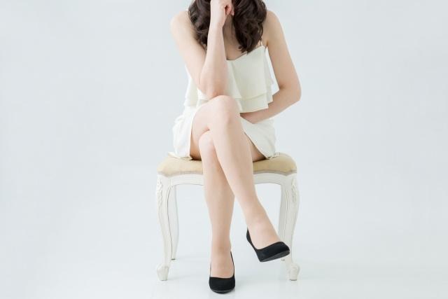 足を前に組んで椅子に座っている女性
