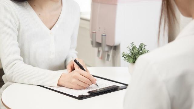 問診票に書き込む女性