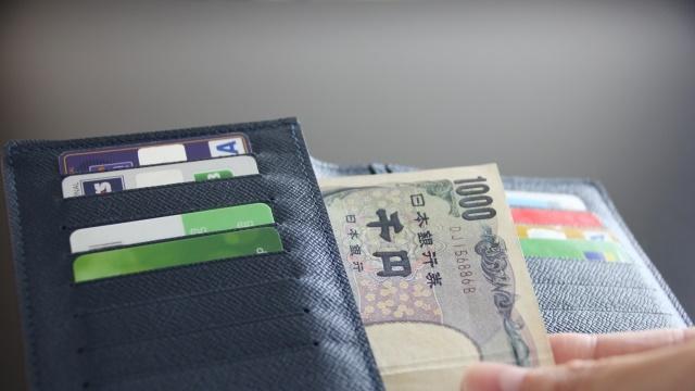 黒い財布から千円札を取り出す
