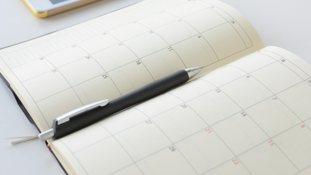 手帳のカレンダーとペンとスマートフォン
