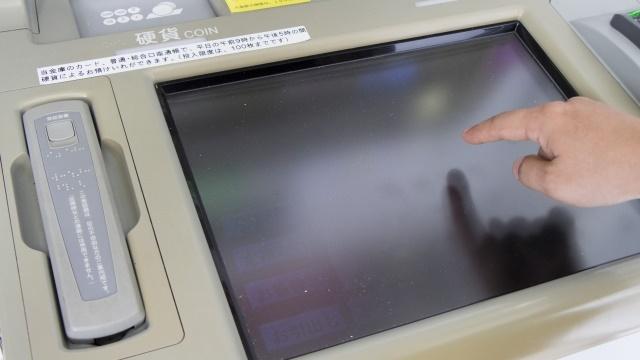 ATMのタッチパネルに触れる