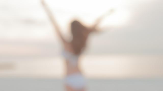 両手を上げる水着を着用した女性