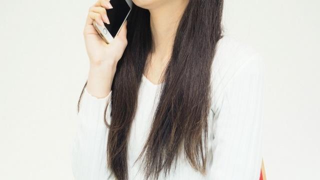 右手にスマートフォンを持つ女性
